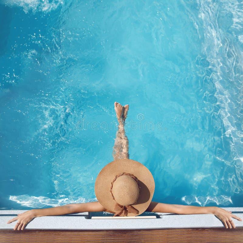 Opinião superior a mulher no chapéu de palha que relaxa na piscina no luxu foto de stock royalty free