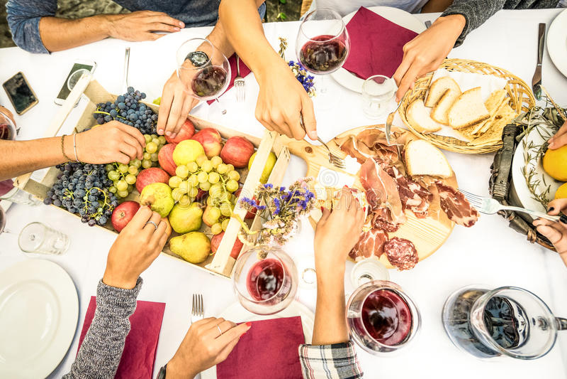 A opinião superior o amigo entrega comer o alimento e o vinho no jardim do assado foto de stock