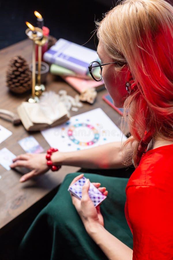 Opinião superior o astrologist louro fêmea que senta-se na tabela e em praticar fotografia de stock