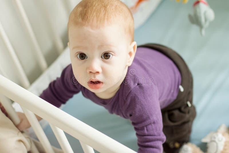 Opinião superior o bebê adorável que tenta levantar-se em seu berço foto de stock royalty free