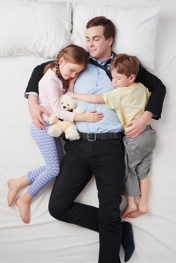 Opinião superior o homem de negócios cansado e as suas duas crianças imagem de stock royalty free