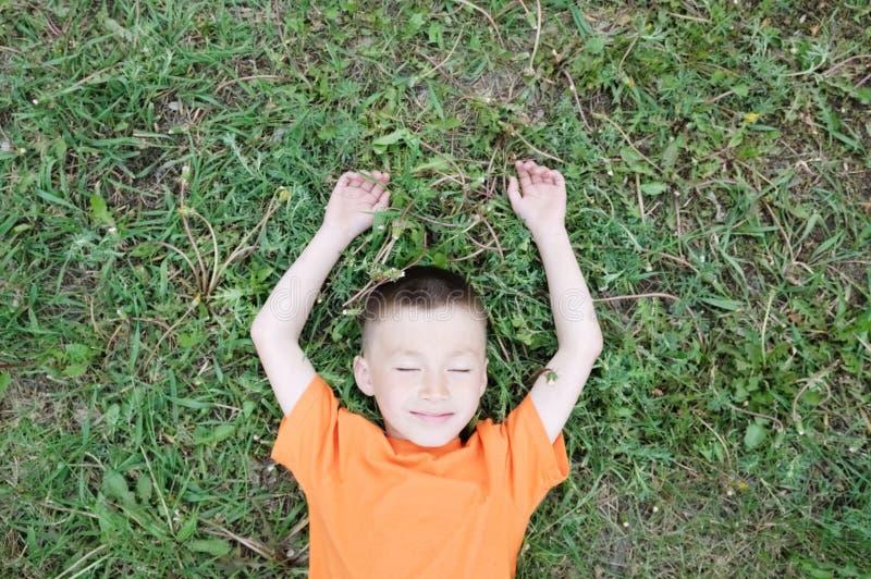 Opinião superior o menino que encontra-se na grama no parque que tem o divertimento A criança relaxa com sorriso Conceito despreo foto de stock