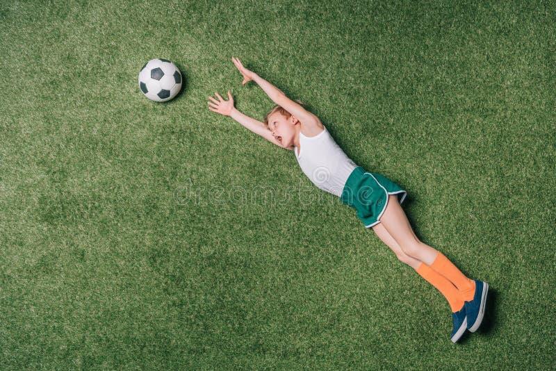 Opinião superior o rapaz pequeno que finge que joga o futebol na grama imagem de stock