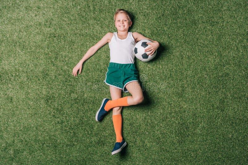 Opinião superior o rapaz pequeno que guarda a bola de futebol na grama imagens de stock royalty free