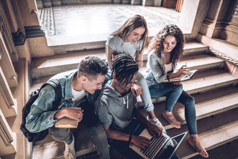 Opinião superior os estudantes que estão passando o tempo junto Jovens que usam o portátil ao sentar-se nas escadas na universida imagens de stock