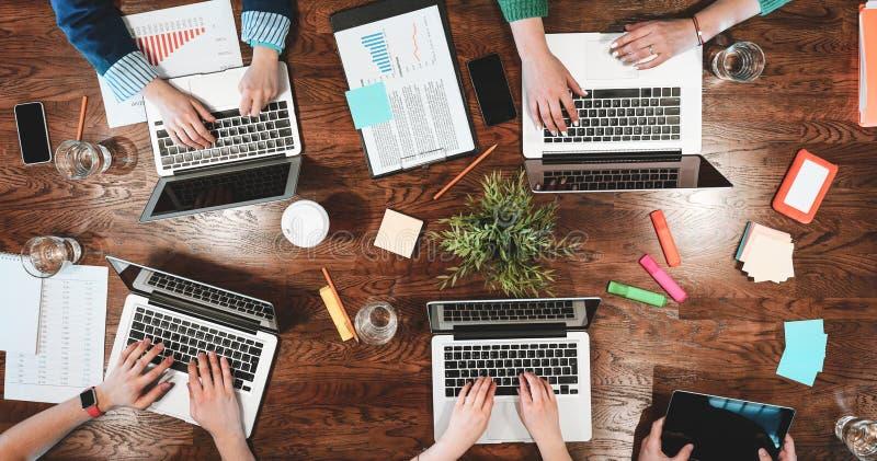 Opinião superior os povos coworking que sentam-se junto em torno da tabela Reunião de negócios de modernos criativos novos A equi imagens de stock