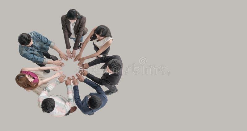 Opinião superior os povos nas mãos da equipe no círculo junto como a unidade e os trabalhos de equipe no escritório imagem de stock royalty free
