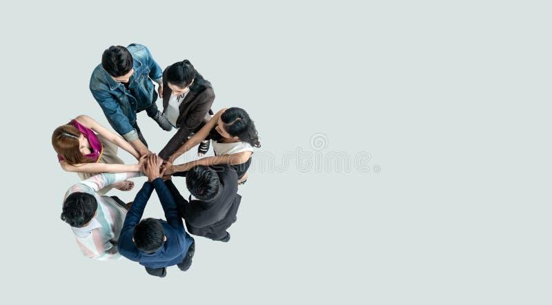 Opinião superior os povos nas mãos da pilha da equipe junto como a unidade e os trabalhos de equipe no escritório foto de stock
