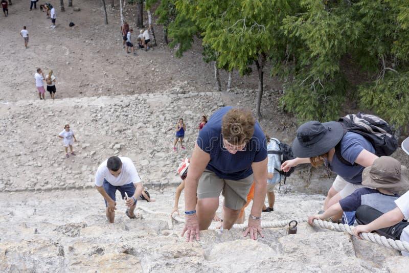 A opinião superior os turistas escala a pirâmide Nohoch Mul ao longo da corda de guiamento nas ruínas maias de Coba, México fotos de stock royalty free