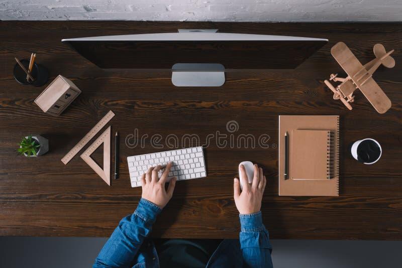 opinião superior parcial a pessoa que datilografa no teclado e que usa o computador de secretária foto de stock royalty free