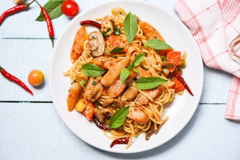 Opinião superior quente e picante dos pimentões do tomate da massa dos espaguetes e das folhas da manjericão/salsicha italiana de imagem de stock
