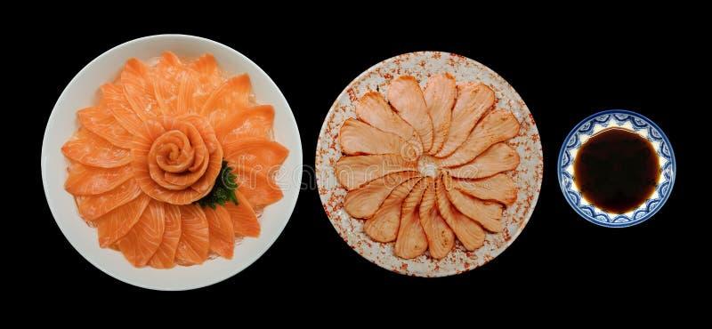 A opinião superior salmões e sashimi frescos da grade e o shoyu servem na forma da flor no barco branco da bacia do gelo isolado  foto de stock