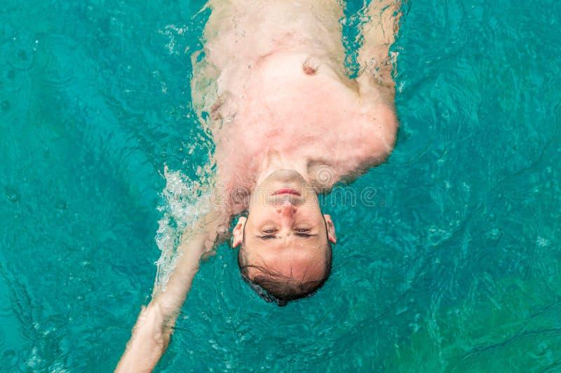 Opinião superior um homem caucasiano novo que nada para trás o rastejamento na piscina foto de stock