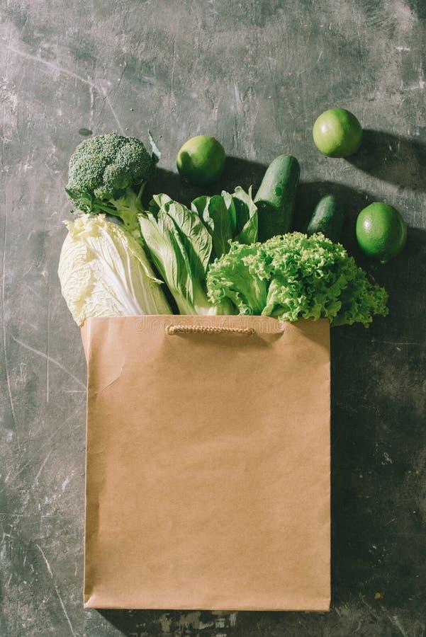 Opinião superior vegetais verdes no saco de compras na tabela de madeira foto de stock royalty free