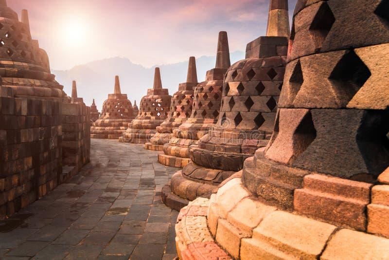 Opinião surpreendente do nascer do sol dos stupas de pedra no templo de Borobudur indonésia imagens de stock royalty free