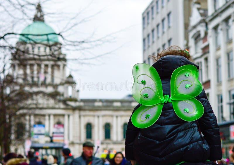 Opinião traseira a criança com as asas da borboleta que têm o símbolo na frente da câmara municipal de Belfast, dia 2018 do trevo fotografia de stock