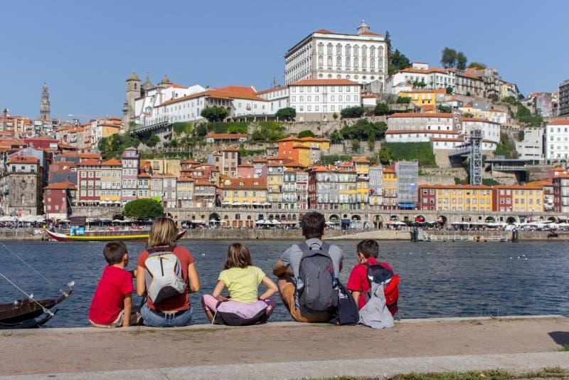 Opinião traseira da família que senta-se na terraplenagem do rio Douro, Porto, Portugal Turistas em Portugal Mochileiros na vista imagem de stock royalty free