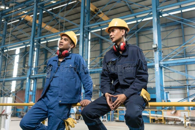 Opinião traseira dois trabalhadores de colarinho azul durante a ruptura fotos de stock royalty free