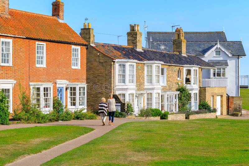Opinião traseira dois turistas fêmeas que andam na cidade popular Southwold do beira-mar do Reino Unido imagens de stock royalty free