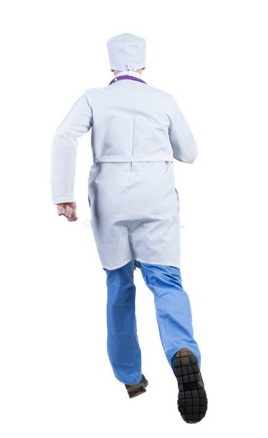 Opinião traseira doutor running em uma veste que apressa-se para ajudar o patie imagem de stock