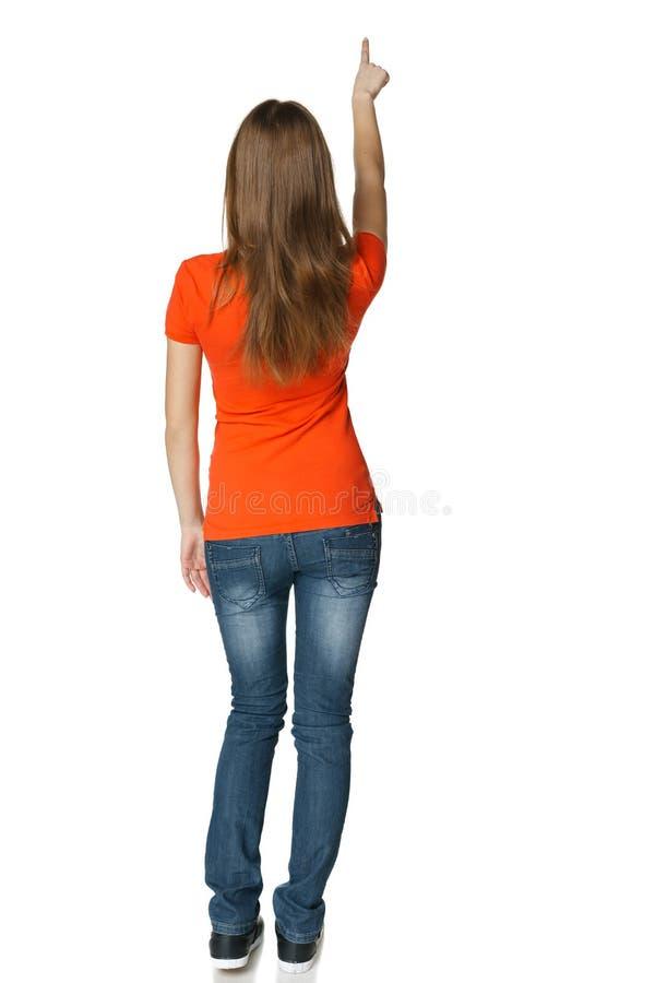 Opinião traseira a fêmea ocasional nova do comprimento completo que aponta no espaço vazio da cópia imagens de stock