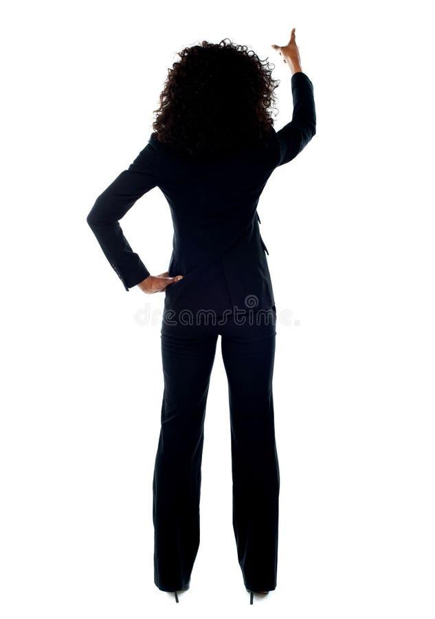 Opinião traseira a fêmea que aponta no espaço da cópia imagem de stock