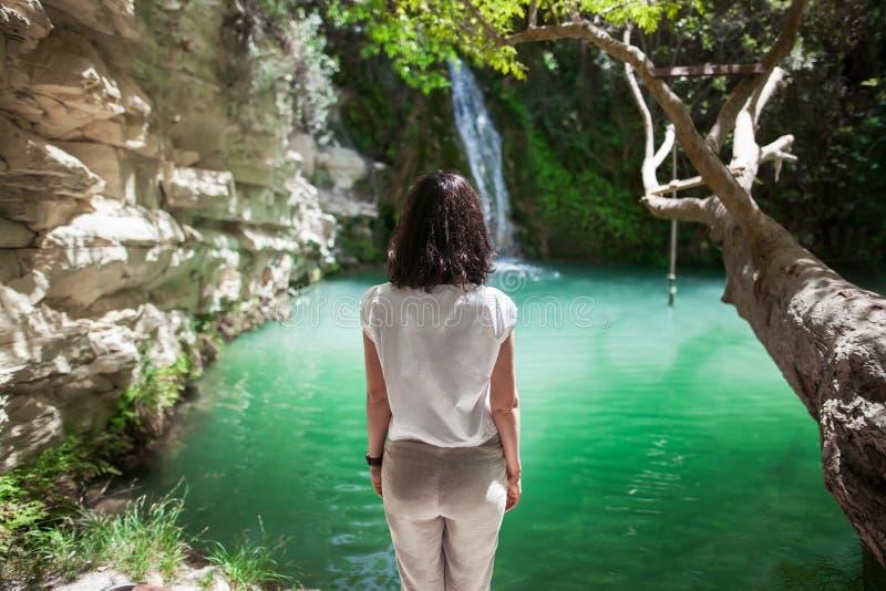A opinião traseira a jovem mulher aprecia a cachoeira no lago bonito imagem de stock royalty free
