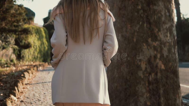 Opinião traseira a jovem mulher que anda apenas no centro de cidade Ir fêmea pensativo perto da estrada no dia ensolarado brilhan fotos de stock