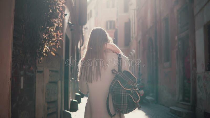 Opinião traseira a jovem mulher que anda na rua da cidade em Europa na manhã Menina que explora a cidade velha sozinha, olhando a foto de stock
