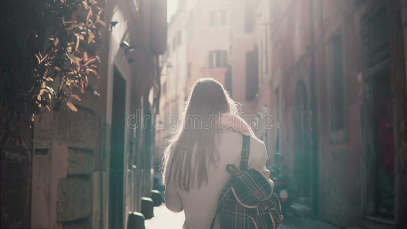 Opinião traseira a jovem mulher que anda na rua da cidade em Europa na manhã Menina que explora a cidade velha sozinha, olhando a fotos de stock
