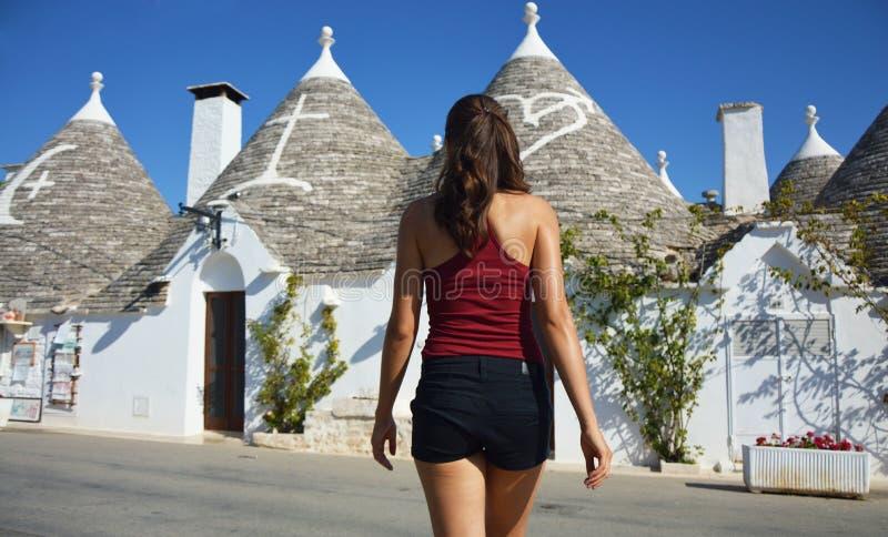 Opinião traseira a jovem mulher que escolhe um trullo Menina que olha telhados do trulli de Alberobello no curso em Itália sul fotos de stock royalty free