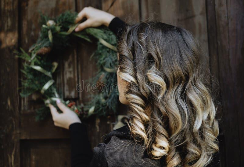 Opinião traseira a jovem mulher que pendura uma grinalda do Natal em sua casa imagem de stock royalty free