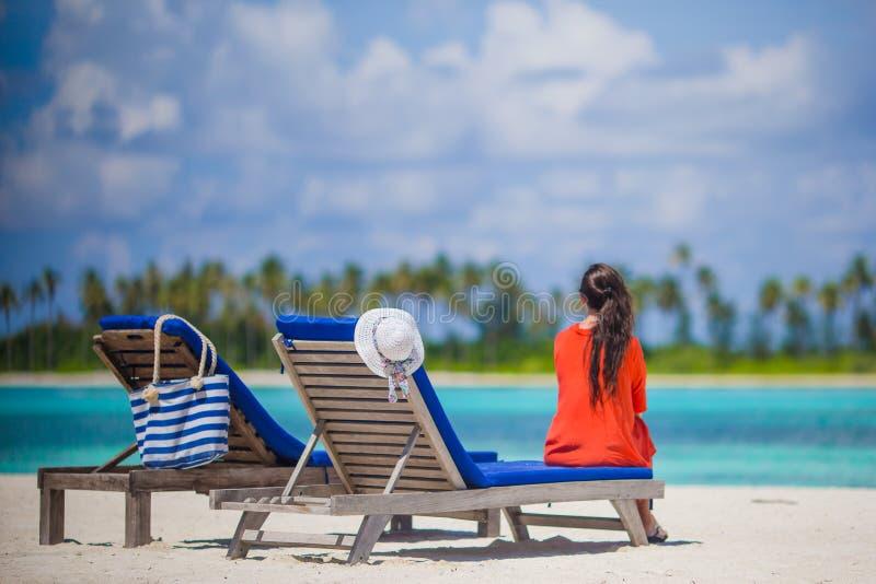 Opinião traseira a jovem mulher que relaxa em cadeiras de praia foto de stock royalty free