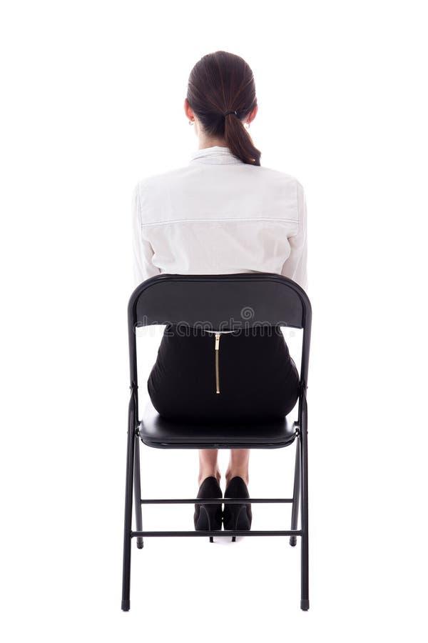 Opinião traseira a jovem mulher que senta-se na cadeira do escritório isolada no whi fotografia de stock