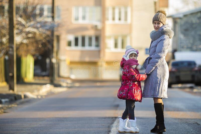 Opinião traseira a mãe atrativa magro nova da mulher e a filha pequena da menina da criança na roupa morna que andam guardando as foto de stock royalty free
