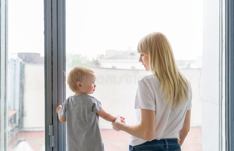 Opinião traseira a mãe e sua filha pequena, olhando se e o sorriso imagens de stock royalty free
