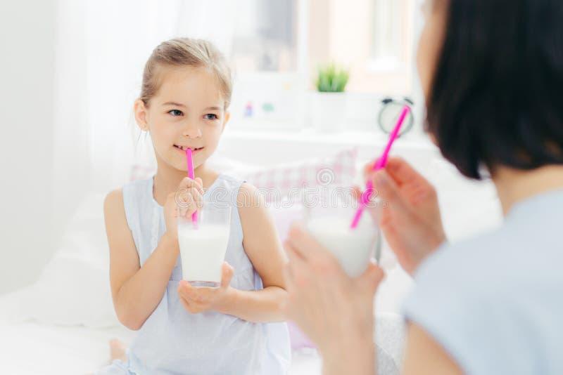 A opinião traseira a mãe moreno nova olha sua filha pequena, bebe cocktail frescos do leite na cama, deleitou expressões e fotos de stock