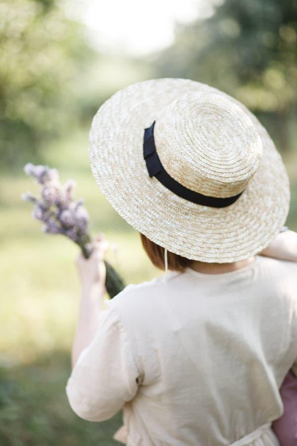 Opinião traseira a mamã Mantém a criança e as flores foto de stock royalty free