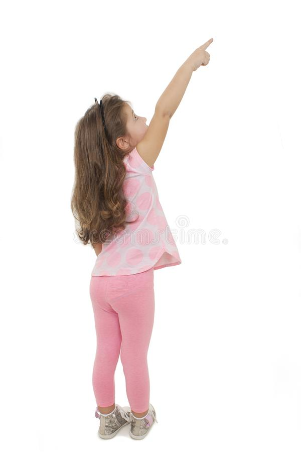 Opinião traseira a menina adorável que aponta o espaço vazio da cópia Vista traseira imagem de stock