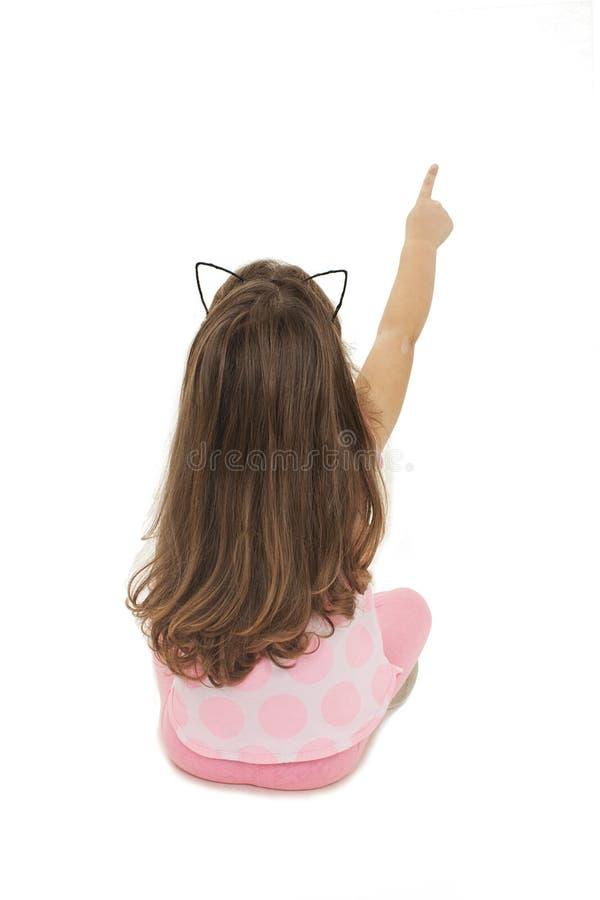 Opinião traseira a menina adorável que aponta o espaço vazio da cópia Vista traseira imagem de stock royalty free