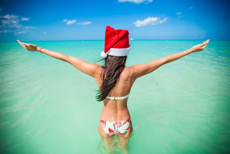 Opinião traseira a menina bonita no passeio do chapéu de Santa fotografia de stock