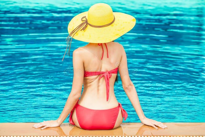 Opinião traseira a menina bonita no roupa de banho vermelho que descansa perto do poo fotos de stock