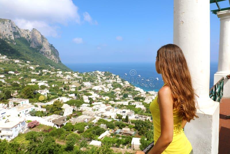 Opinião traseira a menina bonita que olha a vista de Capri do terraço, ilha de Capri, Itália fotografia de stock royalty free