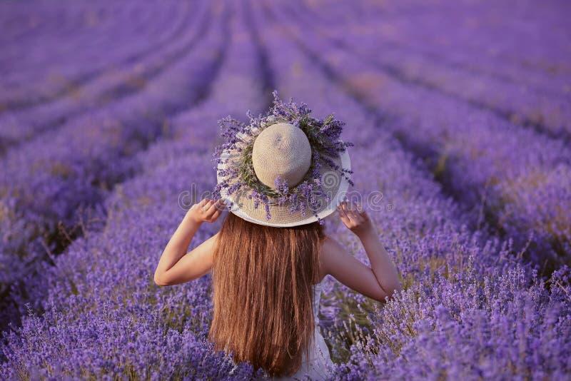 Opinião traseira a menina do jovem adolescente no chapéu sobre o campo da alfazema C feliz imagens de stock