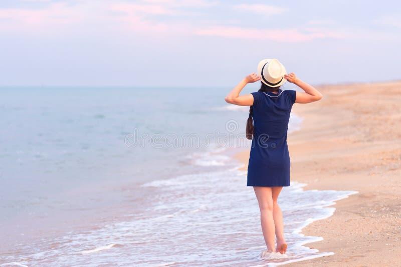 Opinião traseira a menina na praia do mar fotografia de stock