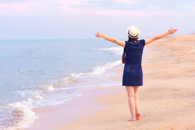Opinião traseira a menina na praia do mar foto de stock