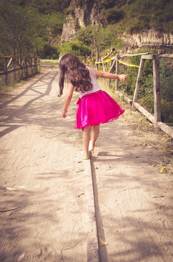 Opinião traseira a menina no passeio cor-de-rosa do vestido fotografia de stock