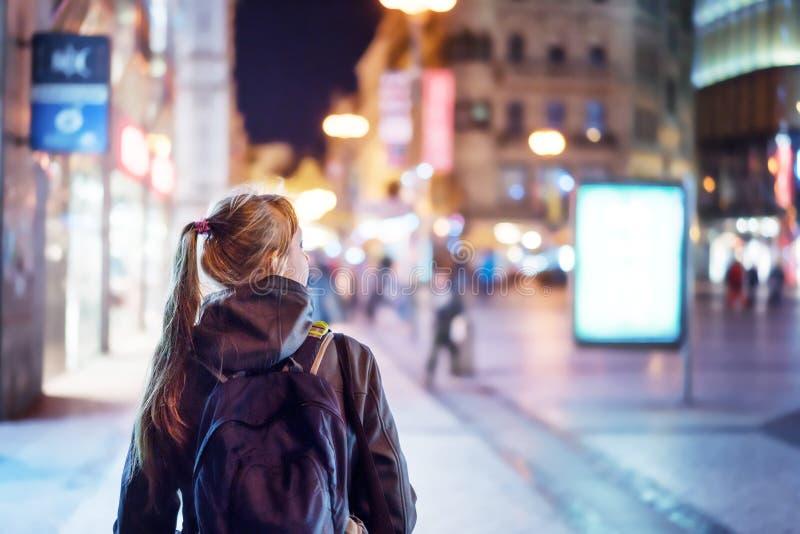 Opinião traseira a menina que anda na rua da cidade na noite imagem de stock royalty free