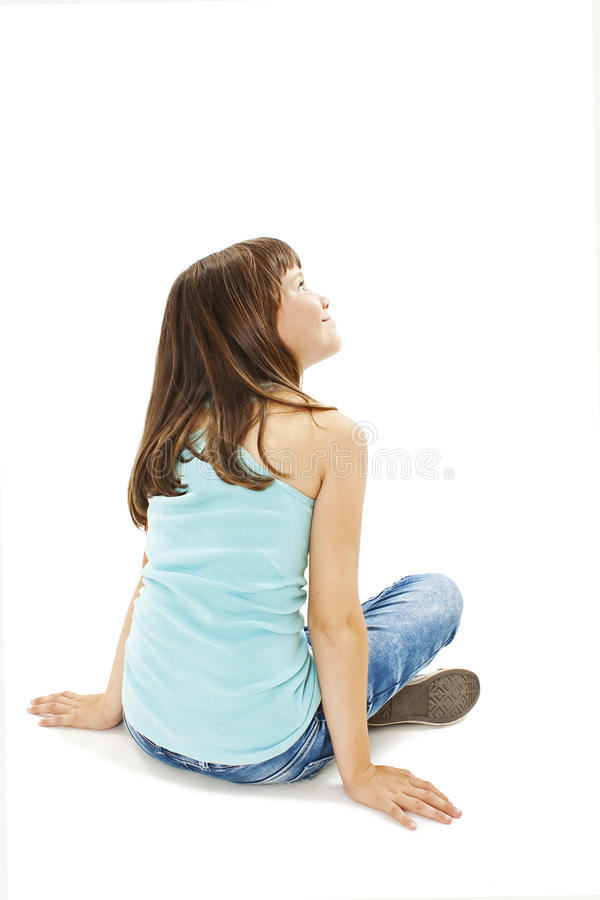 Opinião traseira a menina que senta-se no assoalho, olhando acima fotografia de stock