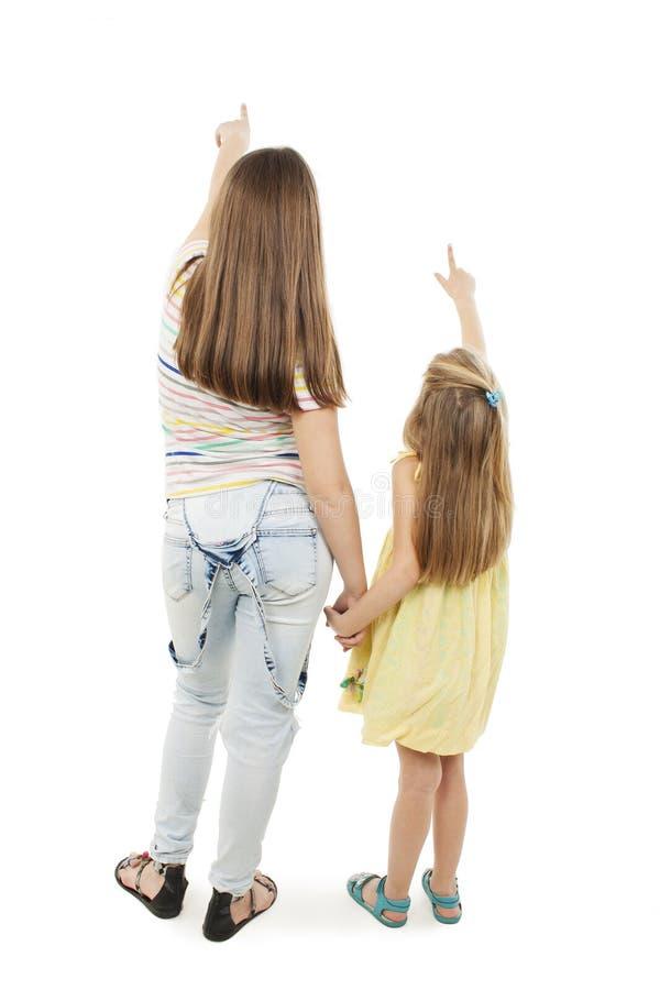 Opinião traseira a moça dois que aponta na parede Irmã dois que guarda as mãos namoradas bonitas que mostram o gesto foto de stock